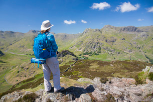 Hiker on summit of Lingmoor Fell, the Langdale Pikes beyond, Great Langdale, Lake District Nationalの写真素材 [FYI03798068]