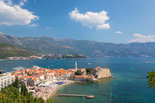 View over crowded beach to the Old Town (Stari Grad), and Budva Bay, Budva, Montenegro, Europeの写真素材 [FYI03798070]