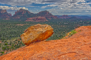 A boulder balanced on the edge of a cliff in Sedona with the Twin Buttes and Cathedral Rock in the dの写真素材 [FYI03798111]