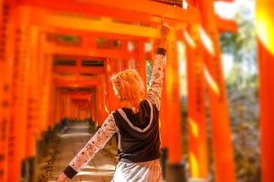 Woman walking beneath red torii gates at Fushimi Inari Shinto shrine, Kyoto, Japan, Asiaの写真素材 [FYI03798284]