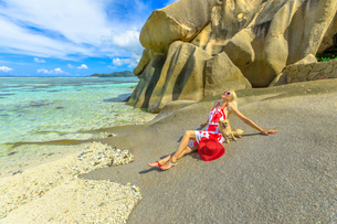 Tourist woman and cute dog sitting on beach at low tide, with granite rocks behind, at Anse Source dの写真素材 [FYI03798302]