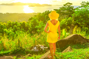 Tourist woman in yellow dress enjoying view of Praslin Island from top viewpoint of La Digue at sunsの写真素材 [FYI03798314]