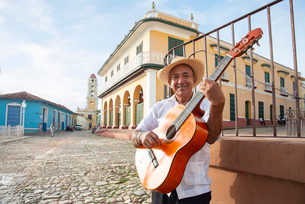Local man singing and playing his guitar in the Plaza Mayor of Trinidad, UNESCO World Heritage Site,の写真素材 [FYI03798346]
