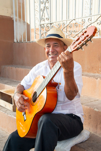 Local man singing and playing his guitar in the Plaza Mayor of Trinidad, Cuba, West Indies, Caribbeaの写真素材 [FYI03798350]
