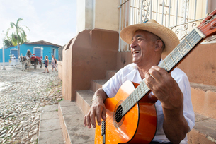 Local man singing and playing his guitar in the Plaza Mayor of Trinidad, Cuba, West Indies, Caribbeaの写真素材 [FYI03798351]