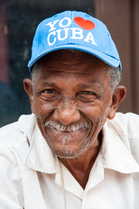 Local man wearing an I love Cuba hat relaxing on the street in Trinidad, Cuba, West Indies, Caribbeaの写真素材 [FYI03798352]