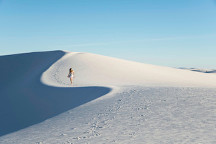 Woman walking along a white sand dune, cast in blue late-afternoon light, in White Sands National Moの写真素材 [FYI03798373]