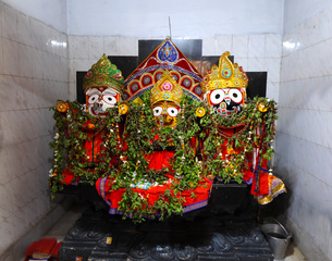 Trio of deities draped with leaf garlands inside temple to Lord Jagannath, rural Odisha, India, Asiaの写真素材 [FYI03799151]