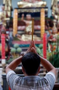 Man praying to the Buddha holding incense sticks, Tay An temple, Chau Doc, Vietnam, Indochina, Southの写真素材 [FYI03799208]
