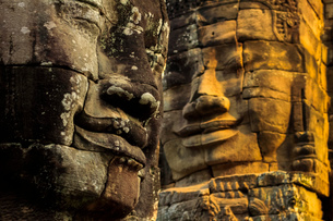 T wo of 216 smiling sandstone faces at 12th century Bayon, King Jayavarman VII's last temple in Angkの写真素材 [FYI03799308]