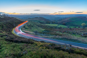 Light trails on road through Peak District National Park, England, Europeの写真素材 [FYI03799383]