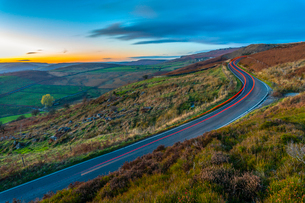 Light trails on road through Peak District National Park, England, Europeの写真素材 [FYI03799386]