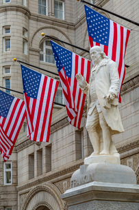 View of Benjamin Franklin statue and US flags in front of former Old Post Office Pavilion, Washingtoの写真素材 [FYI03799525]