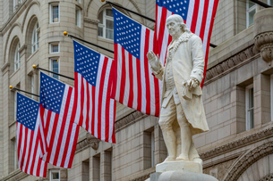 View of Benjamin Franklin statue and US flags in front of former Old Post Office Pavilion, Washingtoの写真素材 [FYI03799527]