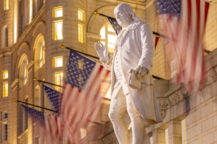 View of Benjamin Franklin statue and US flags in front of former Old Post Office Pavilion, Washingtoの写真素材 [FYI03799534]
