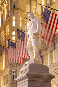 View of Benjamin Franklin statue and US flags in front of former Old Post Office Pavilion, Washingtoの写真素材 [FYI03799535]