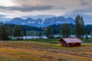 View of traditional log cabin and Kaiser Mountain Range backdrop at Schwarzsee near Kitzbuhel, Tyrolの写真素材 [FYI03799621]