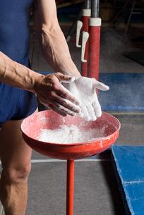 Gymnast putting chalk on his handsの写真素材 [FYI03800129]
