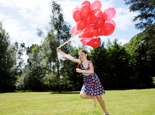 Girl holding bunch of red balloonsの写真素材 [FYI03800326]