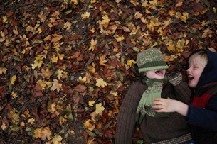 Two friends lying on autumn leavesの写真素材 [FYI03800392]
