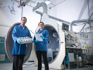 Scientists with product and vacuum tankの写真素材 [FYI03800489]