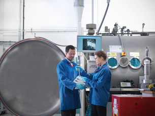 Scientists with product and vacuum tankの写真素材 [FYI03800490]