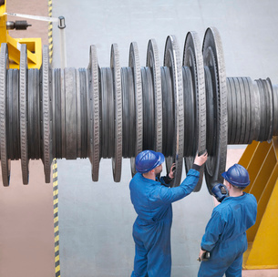 Engineers inspecting turbine  during power station outage, high angle viewの写真素材 [FYI03800580]