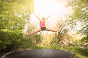 Teenage girl doing star jump on trampoline, outdoorsの写真素材 [FYI03800648]
