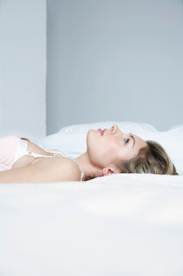 Profile of young woman in underwear lying on bed, close-upの写真素材 [FYI03800668]