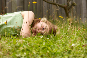 Girl lying on garden grass daydreamingの写真素材 [FYI03800691]