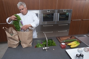 Mid- adult chef unpacking groceriesの写真素材 [FYI03800743]