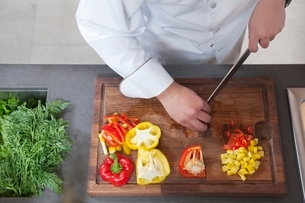 Mid- adult chef dices red and yellow bell peppersの写真素材 [FYI03800747]