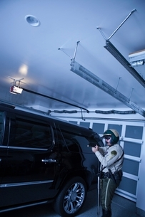Nightwatch patrolman checks luxury car in garageの写真素材 [FYI03800770]