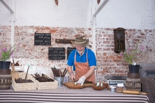 Mature man prepares speciality sausagesの写真素材 [FYI03800813]