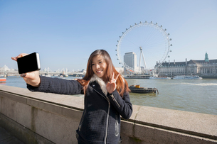 Happy woman taking self portrait through cell phone against London Eye at London, England, UKの写真素材 [FYI03800852]