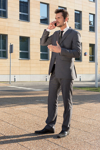 Full length of businessman using cell phone against office buildingの写真素材 [FYI03800861]