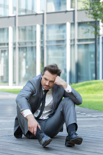 Full length of stressed businessman sitting on path outside officeの写真素材 [FYI03800862]