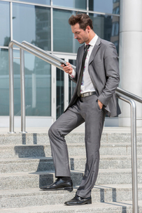 Full length of businessman text messaging through cell phone while standing on steps outside officeの写真素材 [FYI03800868]