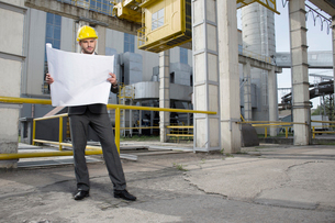 Full length of young male architect examining blueprint outside industryの写真素材 [FYI03800877]