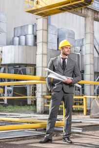 Full length of young businessman with building plans outside industryの写真素材 [FYI03800879]