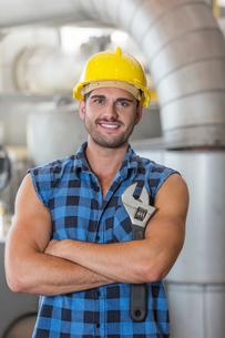 Portrait of confident industrial worker standing arms crossedの写真素材 [FYI03800883]
