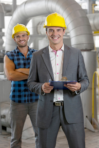 Portrait of smiling young male manager holding clipboard with worker in background at industryの写真素材 [FYI03800885]