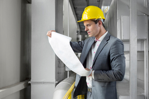 Young male architect examining blueprint in industryの写真素材 [FYI03800886]