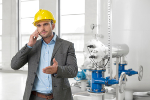 Young male engineer using cell phone in industryの写真素材 [FYI03800888]
