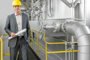 Portrait of young male architect holding blueprint by machinery at industryの写真素材 [FYI03800889]