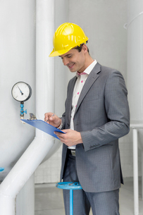 Smiling young male manager writing on clipboard in industryの写真素材 [FYI03800893]