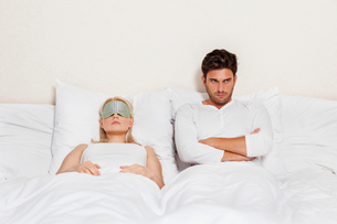 Displeased young man with woman sleeping in bedの写真素材 [FYI03800901]