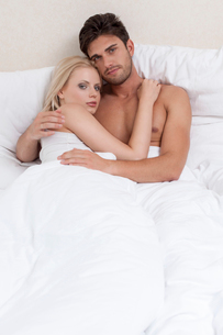 Portrait of young couple embracing in bedの写真素材 [FYI03800914]