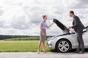 Full length of business couple arguing by broken car at countrysideの写真素材 [FYI03800961]