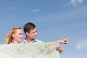 Young man holding map while woman pointing away against skyの写真素材 [FYI03800967]
